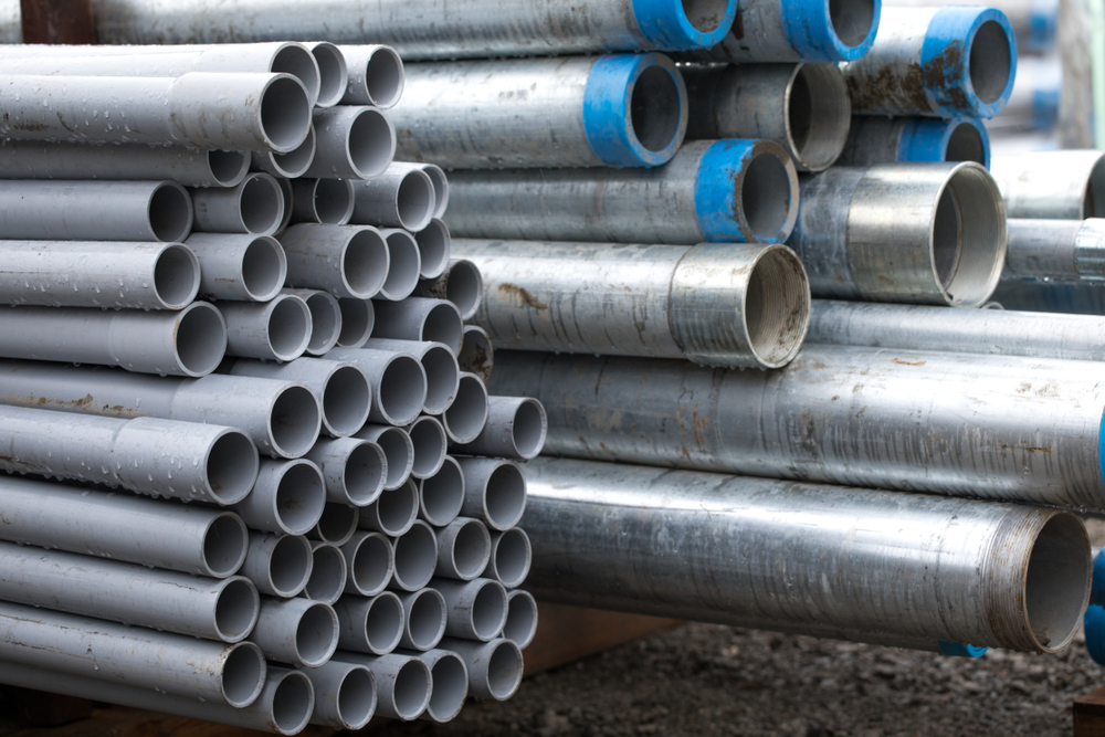 Galvanized steel pipes are in a stack in a warehouse.
