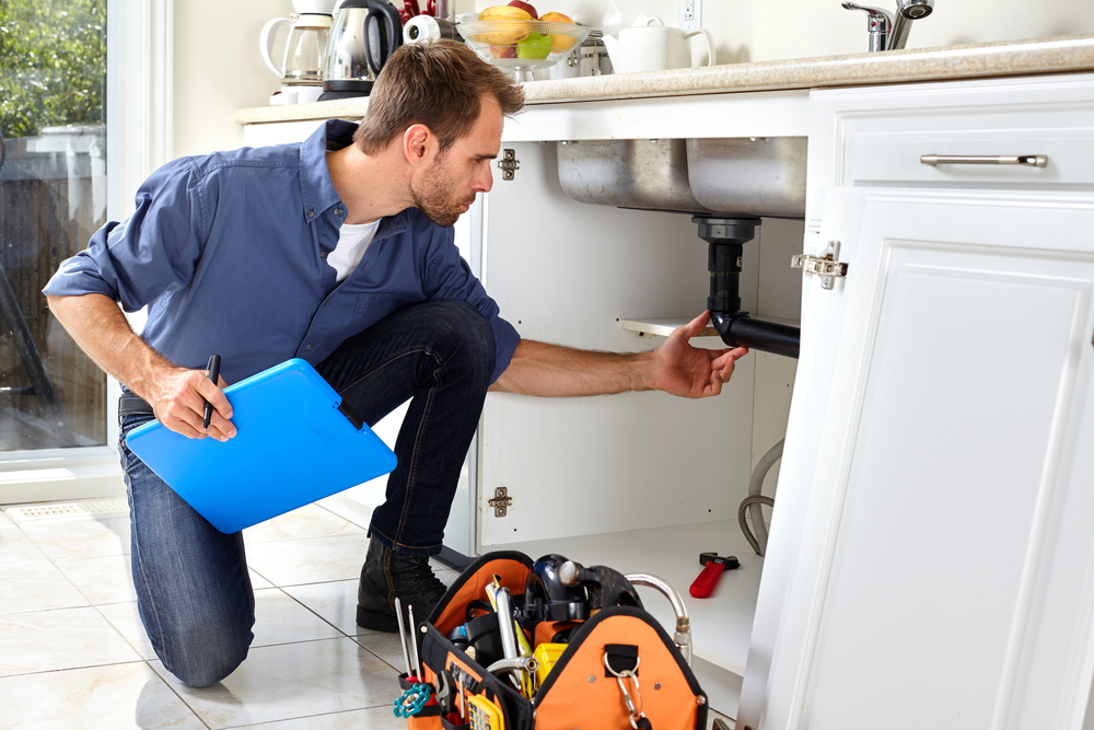 A plumber fixing a kitchen sink's leaking pipe