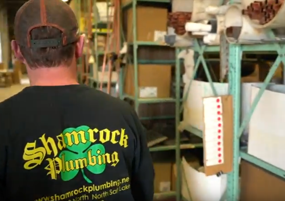 A man wearing a shirt with Utah business Shamrock Plumbing's logo on the back of it